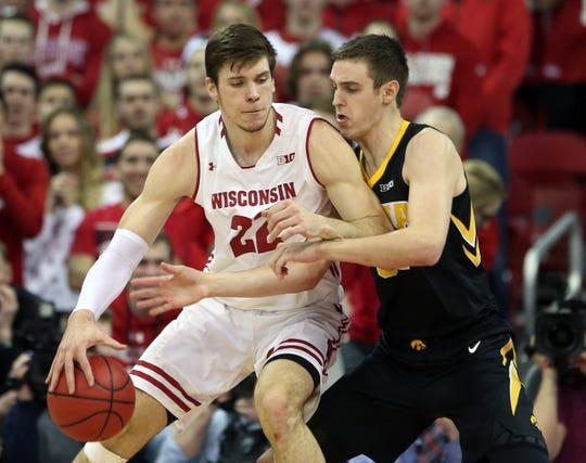 Badgers forward Ethan Happ works against Iowa forward Nicholas Baer.