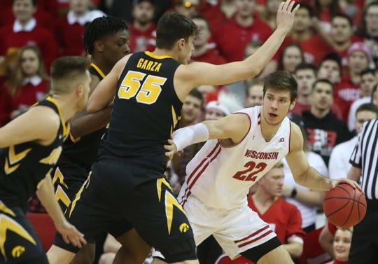 Ethan Happ looks to pass over Iowa forward Luke Garza on Thursday night at the Kohl Center.
