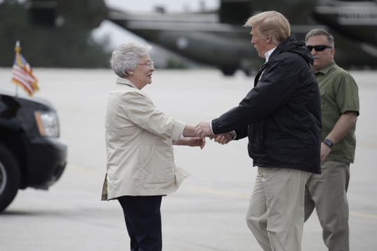 President Donald Trump is greeted by Alabama Gov. Kay Ivey on Trump's arrival, Friday, March 8, 2019, in Auburn, Ala., en route to Lee County, Ala., where tornados killed 23 people.