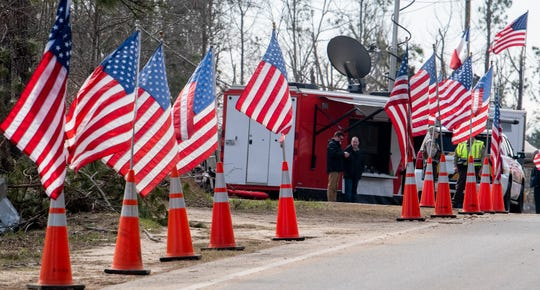 American flags line the route to the tornado damage in Beauregard, Ala., on Friday March 8, 2019. A fatal tornado struck Beauregard on Sunday March 3, 2019. President Donald Trump will visit the area.