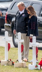 President Donald Trump and First Lady Melania Trump pause at the crosses representing the 23 people killed by the Sunday March 3, 2019 tornado in Beauregard, Ala., during his visit to the area on Friday March 8, 2019.