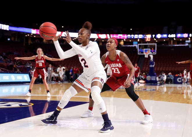 Auburn's Brooke Moore (2) receives the inbound pass while being guarded by Alabama's Shaquera Wade (23) in the Tigers'  53-52 win over the Tide Thursday in the SEC Women;s Basketball Tournament in Greenville, S.C.
