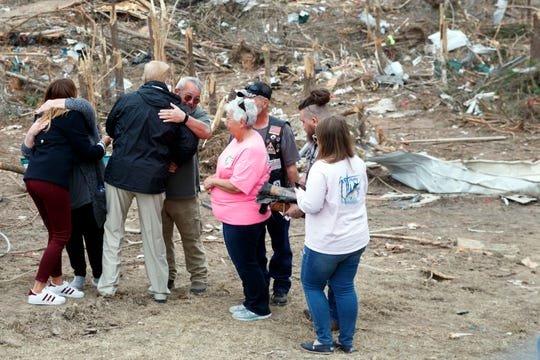 President Donald Trump and first lady Melania Trump hug with people Beauregard, Ala., Friday, March 8, 2019, as they travel to tour areas where tornados killed 23 people in Lee County, Ala. (AP Photo/Carolyn Kaster)