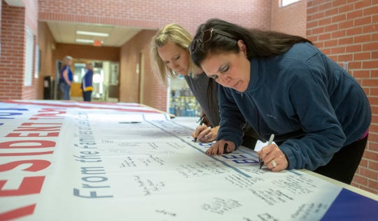 Beauregard residents sign a banner thanking President Donald Trump for coming to the tiny town following a devastating EF-4 tornado.