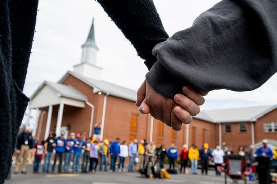 Locals and workers hold hands in a prayer circle at Providence Baptist Church in Beauregard, Ala., on Friday March 8, 2019. A fatal tornado struck Beauregard on Sunday March 3, 2019.