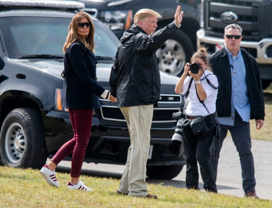 President Donald Trump and First Lady Melania Trump pause and wave to those who came out to see him in Beauregard, Ala., during his visit to the area on Friday March 8, 2019.