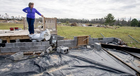 Cindy Sanford stands on the deck of her home, the only thing left of her home, in Beauregard, Ala., on Friday March 8, 2019. A fatal tornado struck Beauregard on Sunday March 3, 2019.