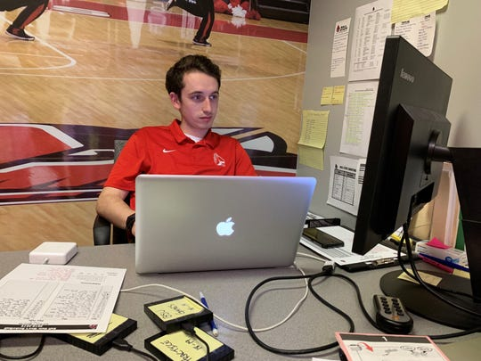 Ball State manager Jason Smith edits film at his desk in the hours after Ball State's game against Miami.