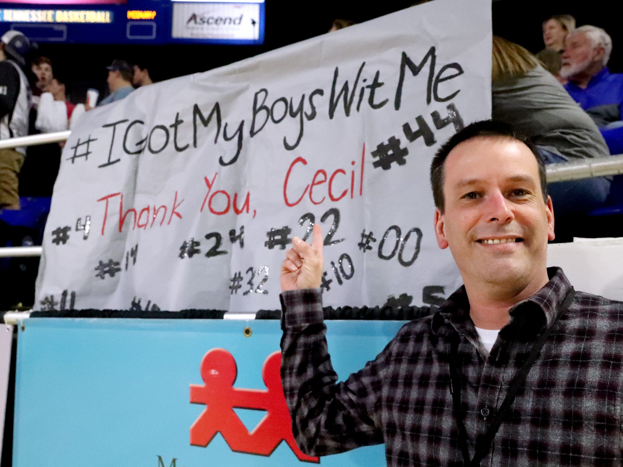 DNJ High School sport writer Cecil Joyce stands next to the Eagleville that thanks him for his coverage of Eagleville through the season, during the quarterfinal round of the TSSAA Div. 1 Class A Girls State Tournament, on Thursday, March 7, 2019, at Murphy Center in Murfreesboro, Tenn.