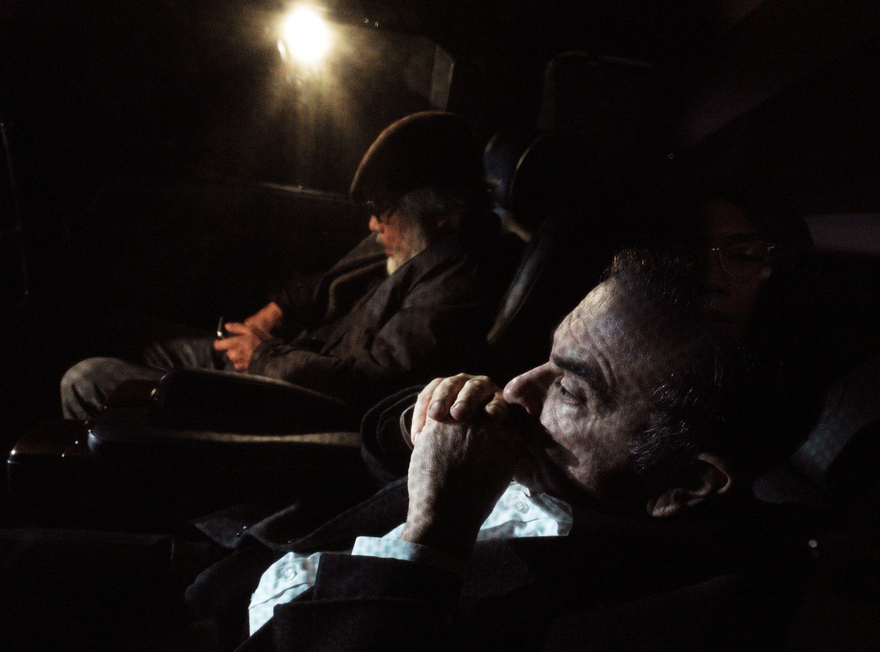 In this March 6, 2019, photo, former Nissan chairman Carlos Ghosn, right, sits with his lawyer Takashi Takano, left, in a car Wednesday, March 6, 2019, in Tokyo, following Ghosn's release. The mystery of Ghosn's strange attire when he was released from Japanese detention has been solved, with his lawyer Takano saying Friday, March 8, that it was an effort to protect the former chairman of Nissan from intense media attention. (AP Photo/Eugene Hoshiko)