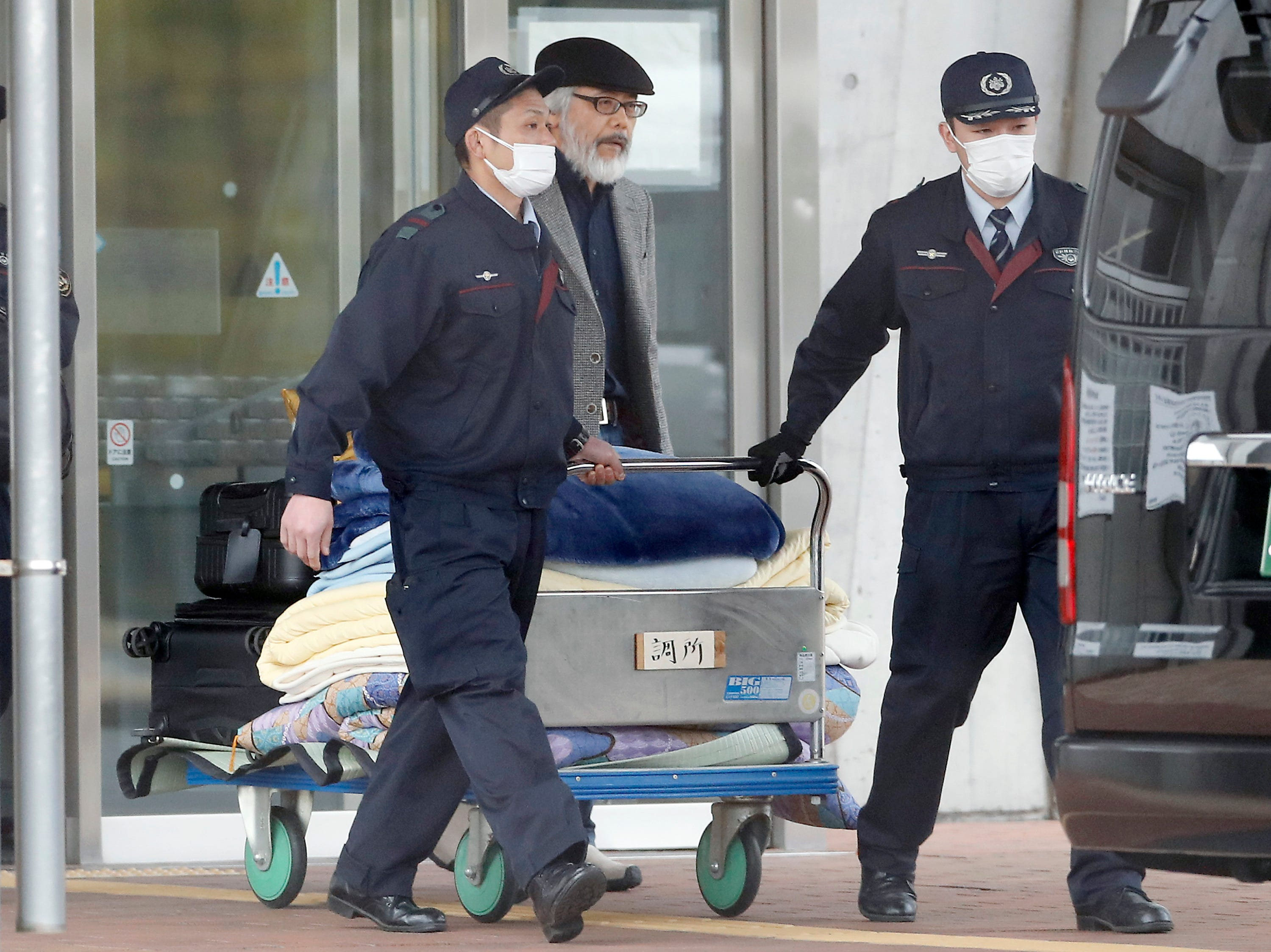 In this March 6, 2019, photo, Takashi Takano, center, lawyer of former Nissan chairman Carlos Ghosn, carries bags and other belonging believed to be of Carlos Ghosn from Tokyo Detention Center in Tokyo. The mystery of Carlos Ghosn's strange attire when he was released from Japanese detention has been solved, with his lawyer Takano saying Friday, March 8, that it was an effort to protect the former chairman of Nissan from intense media attention. (AP Photo/Eugene Hoshiko)