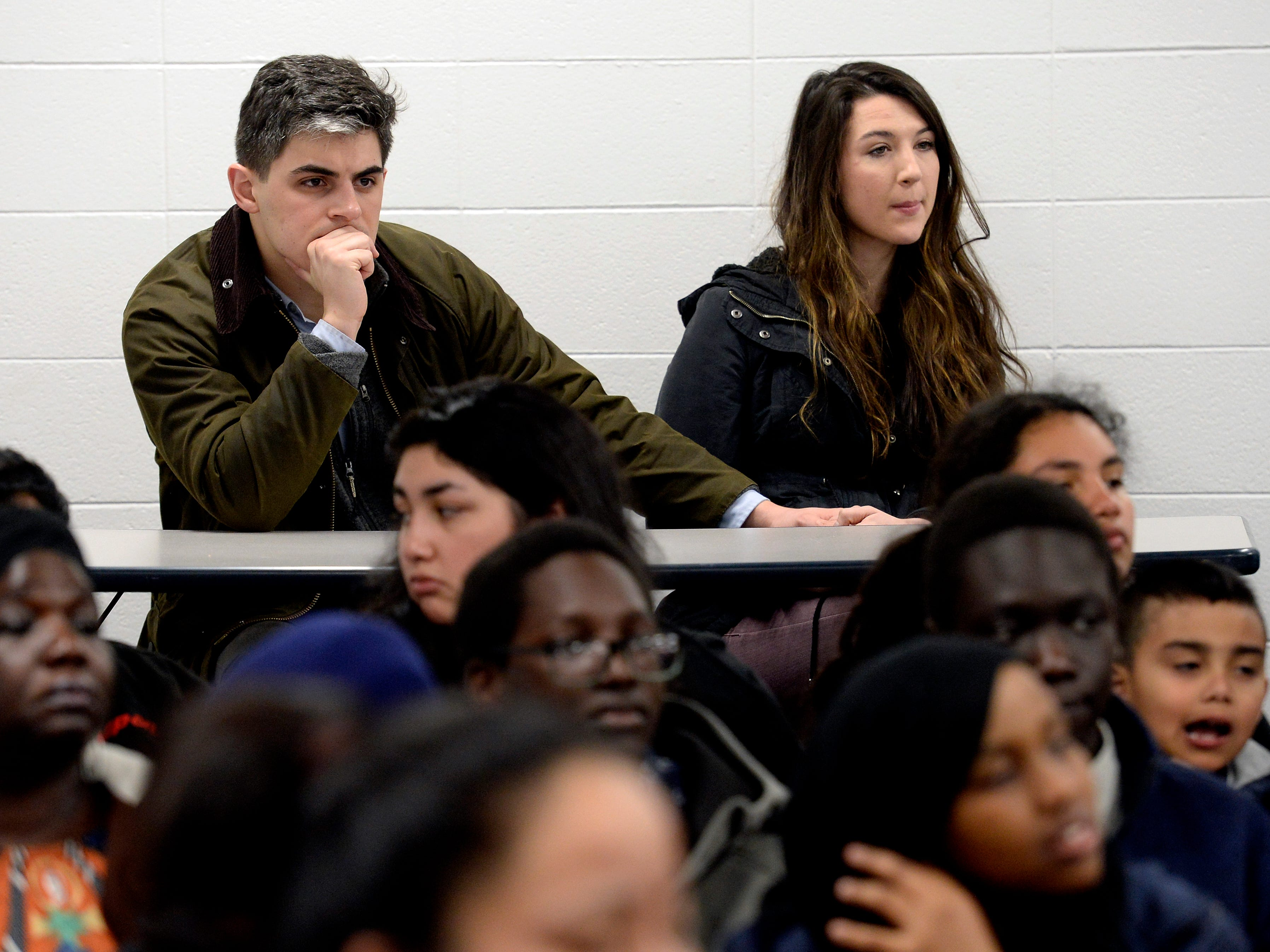 Parents and children listen to speakers during a parent meeting about New Vision Academy charter school on Thursday, March 7, 2019 in Nashville, Tenn.