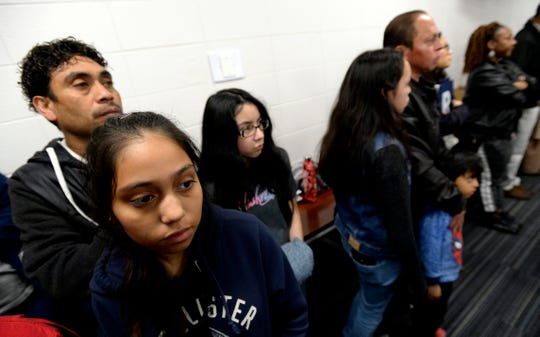 Parents and children listen during a meeting about the midyear closure of New Vision Academy charter school in Nashville, Tennessee.  The school closed this month after a crackdown on fire code violations, financial irregularities and complaints about treatment of English-language learners and students with disabilities.