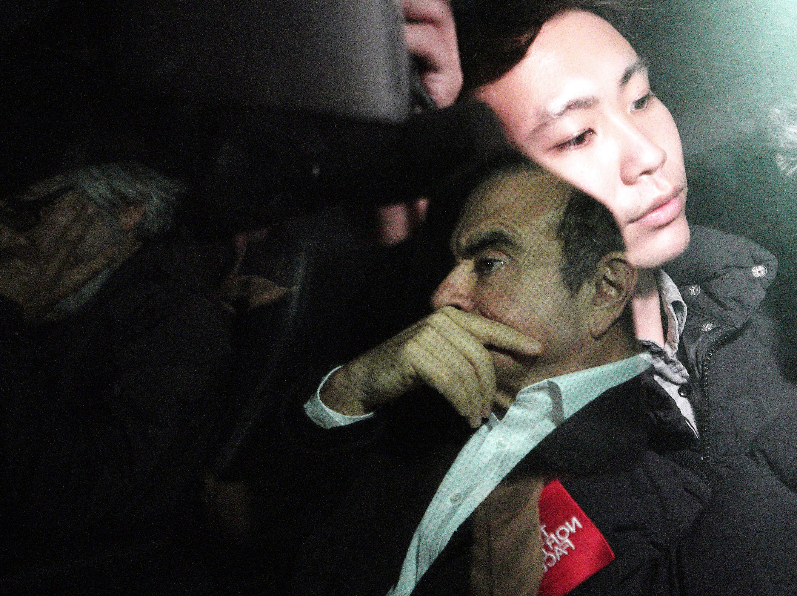 In this March 6, 2019, photo, as a TV crew is reflected on a car window, former Nissan chairman Carlos Ghosn, right, travels with his lawyer Takashi Takano, left, in a car in Tokyo, following his release in Tokyo. The mystery of Ghosn's strange attire when he was released from Japanese detention has been solved, with his lawyer saying Friday, March 8, that it was an effort to protect the former chairman of Nissan from intense media attention. (AP Photo/Eugene Hoshiko)