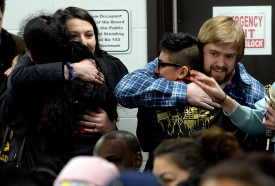 Former teachers at New Vision Academy charter school hug students before a parent meeting on Thursday, March 7, 2019 in Nashville, Tenn.