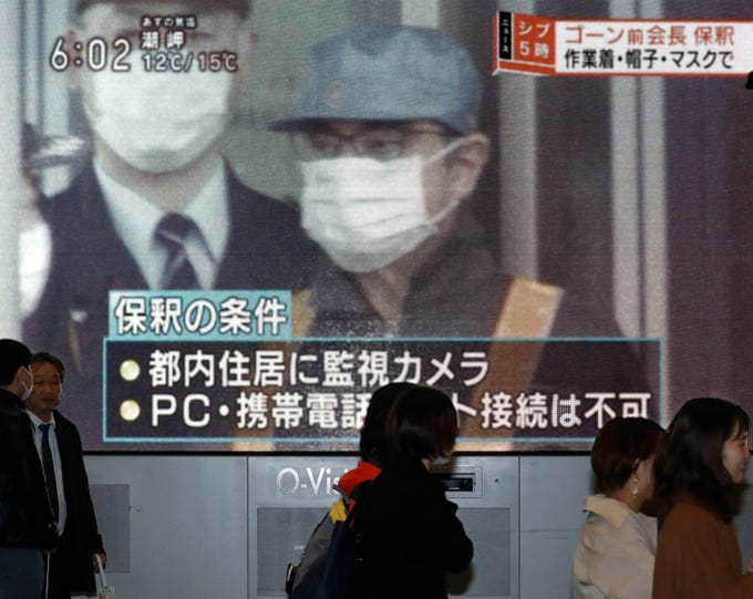 "People walk by a monitor which reports on the bail of former chairman of Nissan Motor Co., Carlos Ghosn, in Osaka, western Japan Wednesday, March 6, 2019. Disguised as a construction worker, Ghosn left a Tokyo detention center Wednesday after posting 1 billion yen ($8.9 million) bail. The letters, bottom, read "" Conditions for his release."" (Kyodo News via AP)"