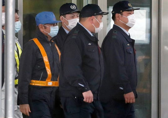 In this March 6, 2019, photo, former Nissan Chairman Carlos Ghosn, in blue cap, walks out with security guards from Tokyo Detention Center in Tokyo. The mystery of Carlos Ghosn's strange attire when he was released from Japanese detention has been solved, with his lawyer Takashi Takano saying Friday, March 8, that it was an effort to protect the former chairman of Nissan from intense media attention. (AP Photo/Eugene Hoshiko)