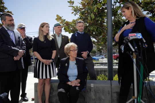 Eva Schloss, center, the stepsister of Anne Frank and a Holocaust survivor, listens to Charlene Metoyer, a board member of the Newport-Mesa Unified School District during a news conference Thursday, March 7, 2019, in Newport Beach, Calif. Schloss has met with Southern California high school students who were photographed giving Nazi salutes around a swastika formed by drinking cups at a party. Schloss says the students apologized for their behavior and indicated they didn't realize what it really meant.