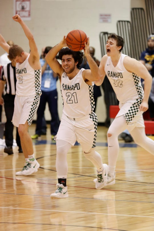 John Whooley (center), KC Hunt (left) and Neal Quinn celebrate in the final seconds of Ramapo's 35-32 win over Colonia in a Group 3 boys basketball semifinal at East Orange Campus on Thursday, March 7, 2019.