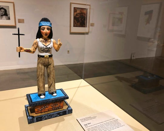 "In this Wednesday, March 6, 2019 photo a wood carving entitled ""La Sad Girl"" by artist Andrew Montoya sits at the National Hispanic Cultural Center in Albuquerque, N.M. before the opening of a exhibit on the chola, a working-class, Mexican-American female often associated with urban gangs. The ""Que Chola Exhibition"" opens on Friday, March 8  with pieces by artists from New Mexico, Arizona, California, Texas, and Colorado."
