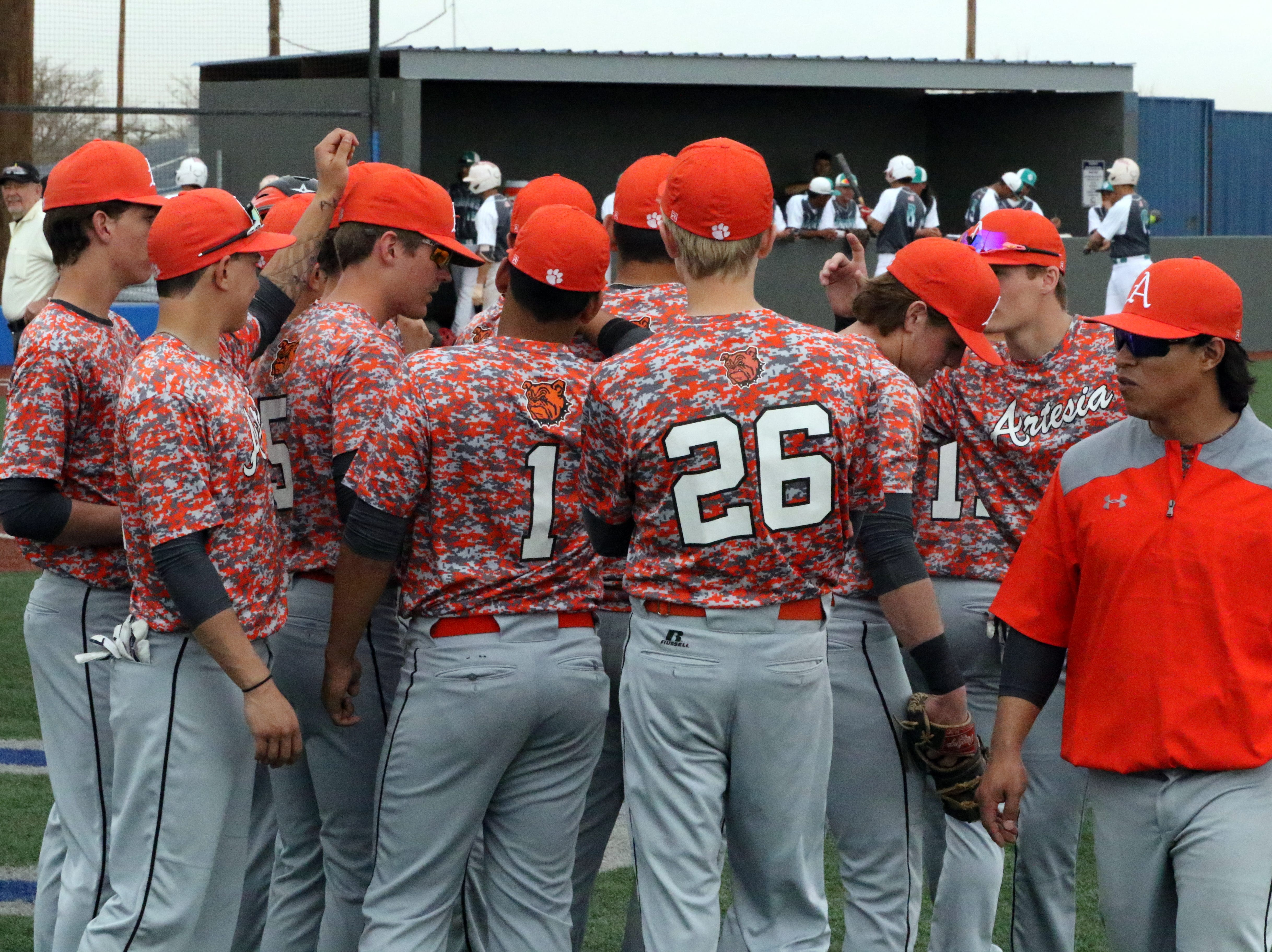 Artesia has one final chat before heading out on the field against Valencia on Thursday. The Bulldogs won, 12-5.