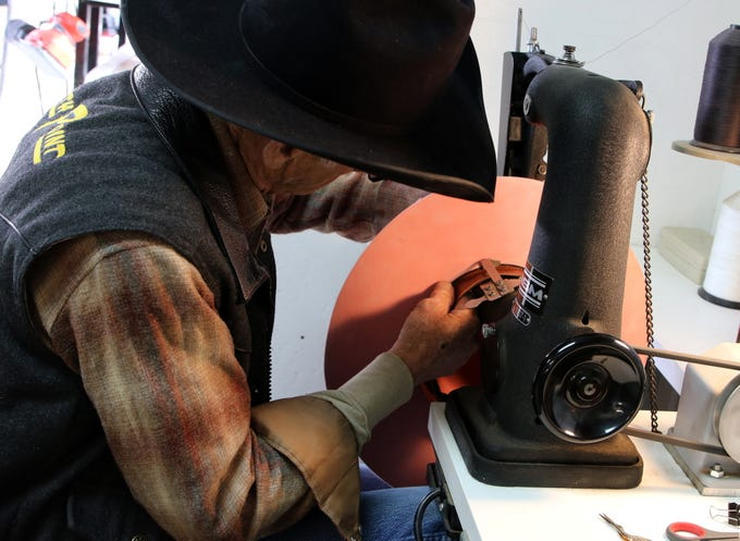Ramie Harper sews the inner band onto a hat he is making for the governor.
