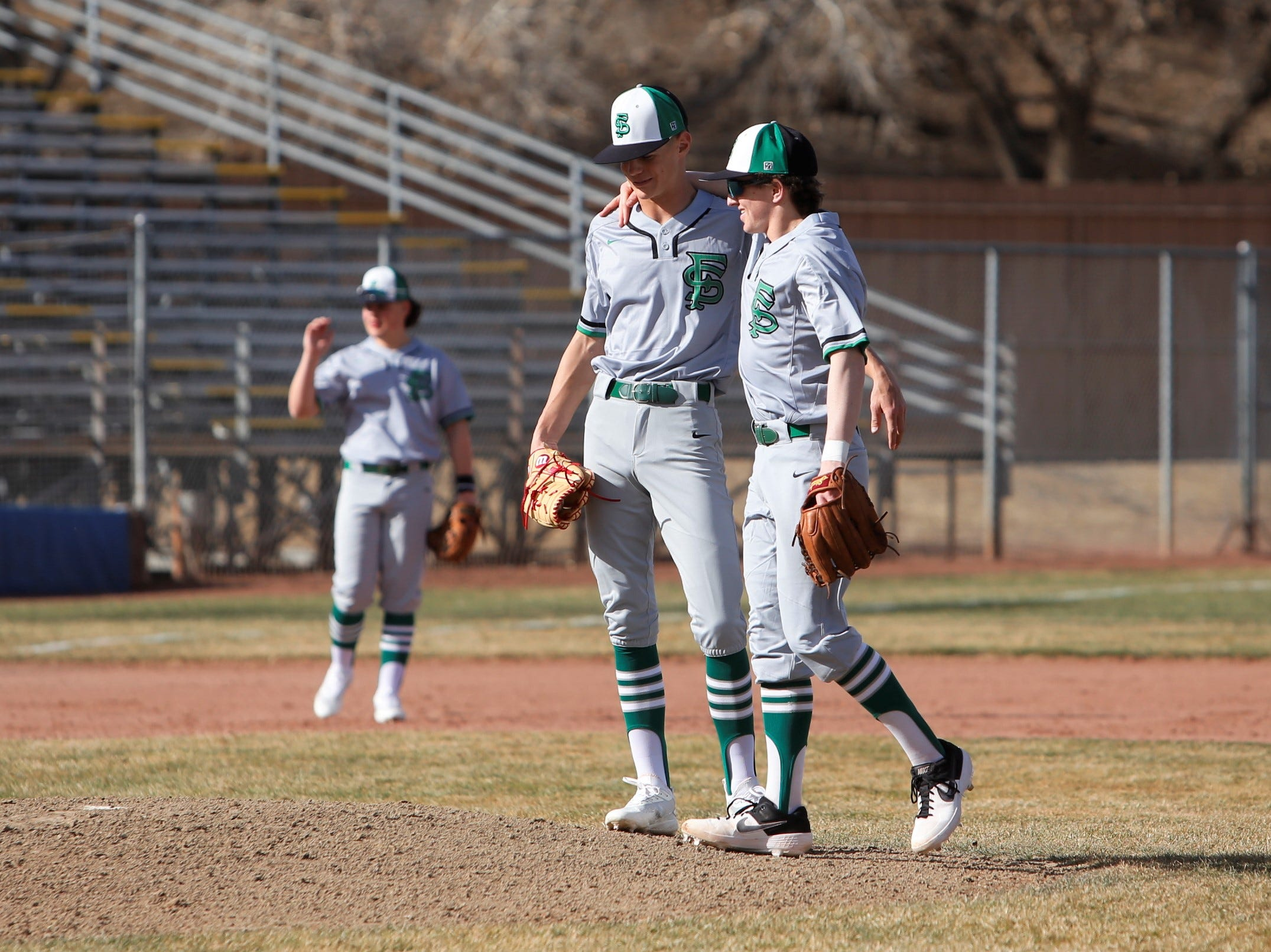 Farmington's Danny Carpenter, right, meets with Bradon Zastrow on the mound in-between at-bats against Los Lunas during Thursday's FHS Scorpion Invitational tournament game at Ricketts Park in Farmington.