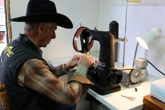 Ramie Harper prepares to sew the inner band into a hat he is making for Gov. Michelle Lujan Grisham.