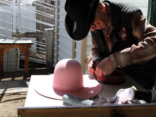 Ramie Harper works on a hat he plans to give Gov. Michelle Lujan Grisham.