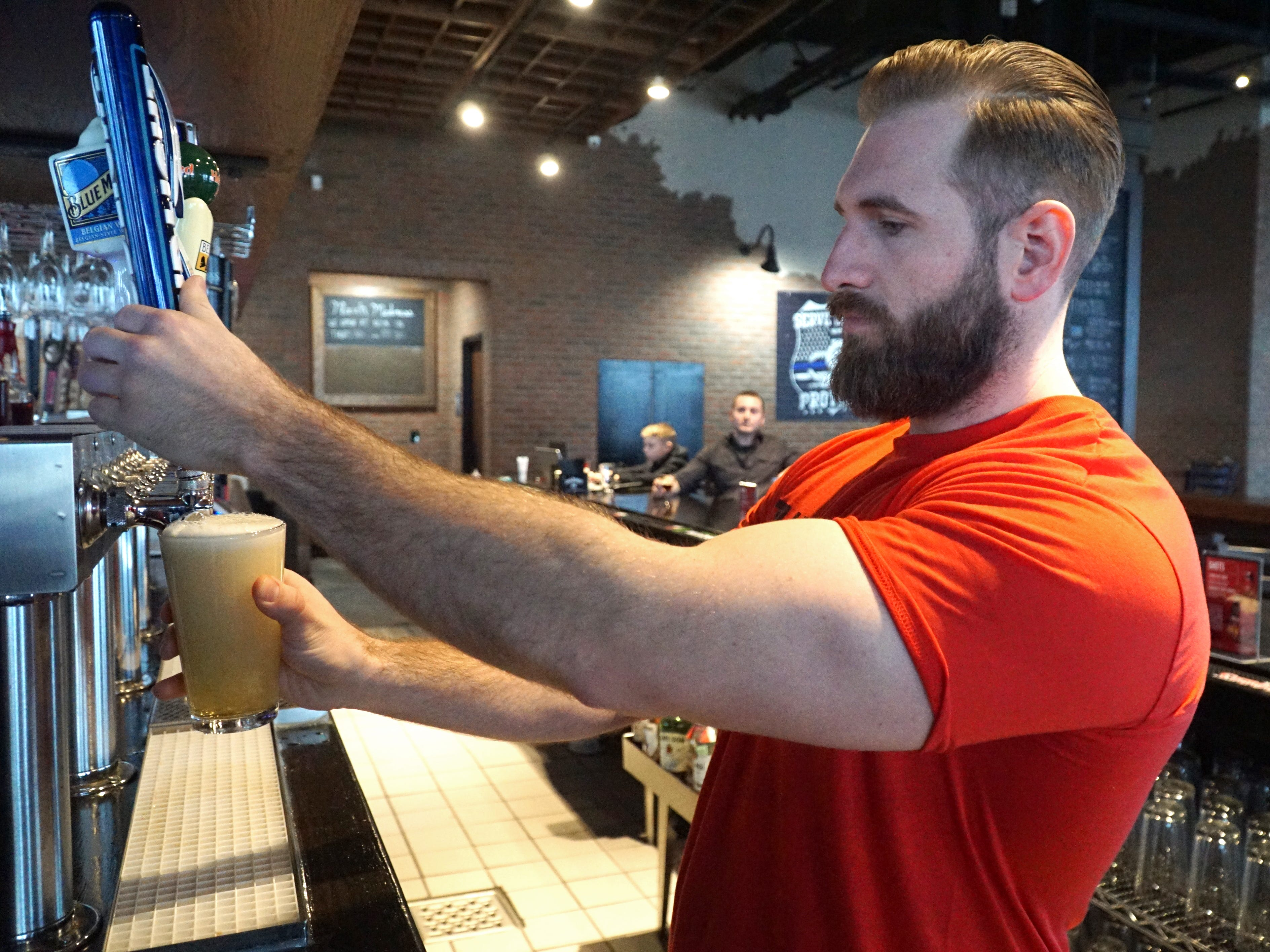 5th Avenue bartender Dan Vercellino pulls a beer from the taps at the Novi bar on March 7.