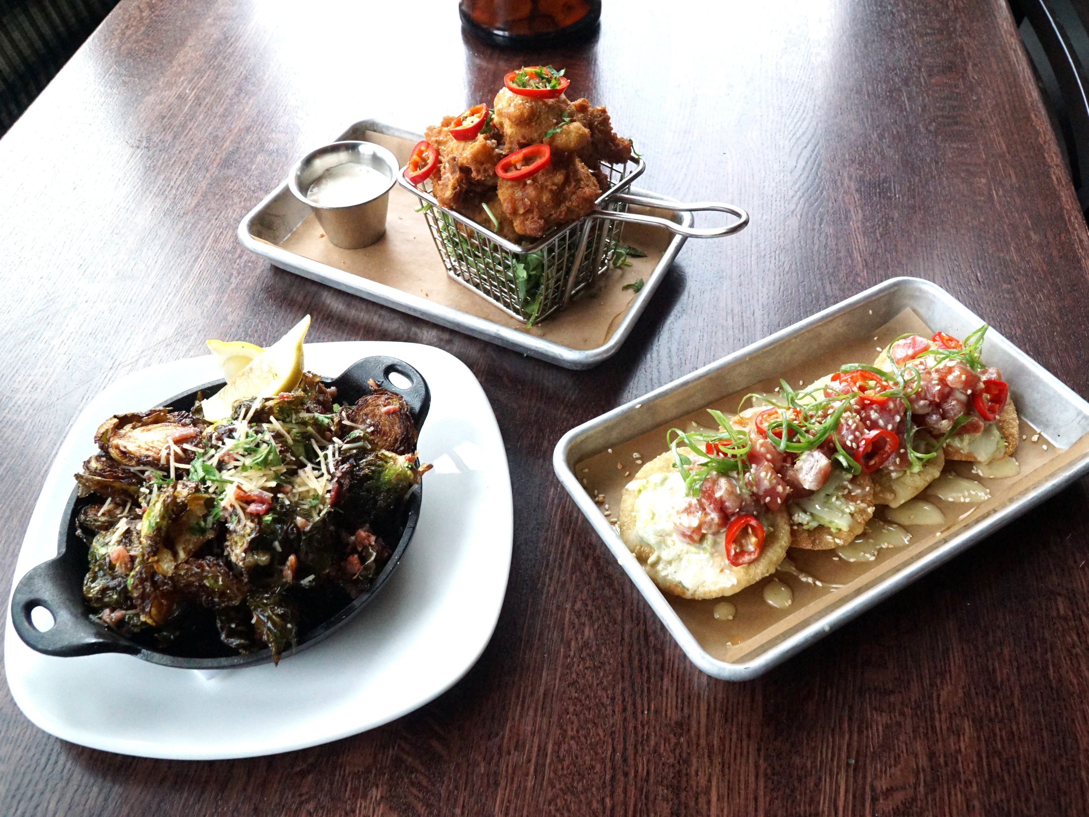 New Granite City menu items include, from left: crispy brussel sprouts, street corn fritters, and poke tuna tostadas.
