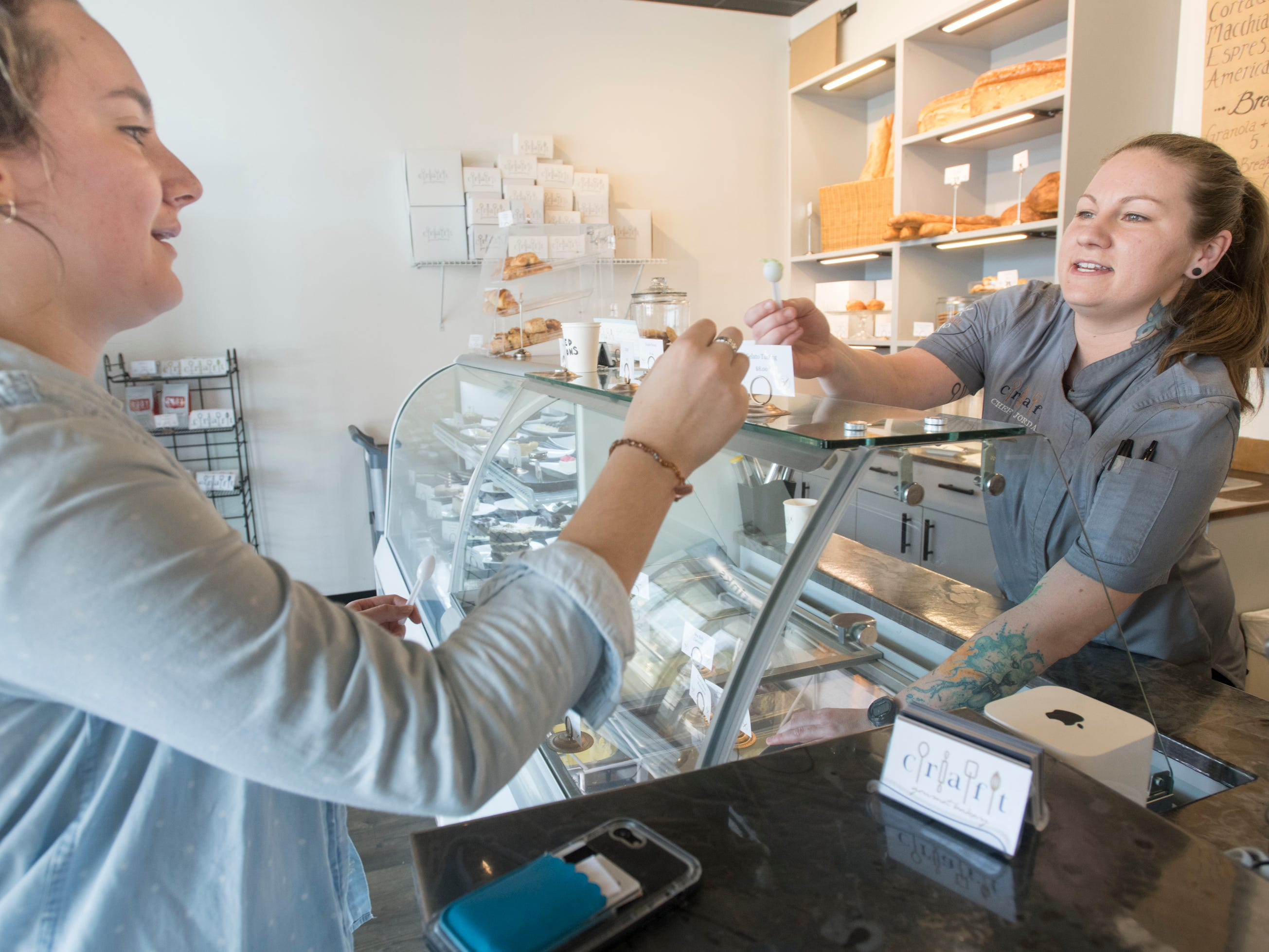 Owner Jordan Hewes, right, hands Sarah Ruscitto a gelato sample at Craft Gourmet Bakery in Pensacola on Friday, March 8, 2019.