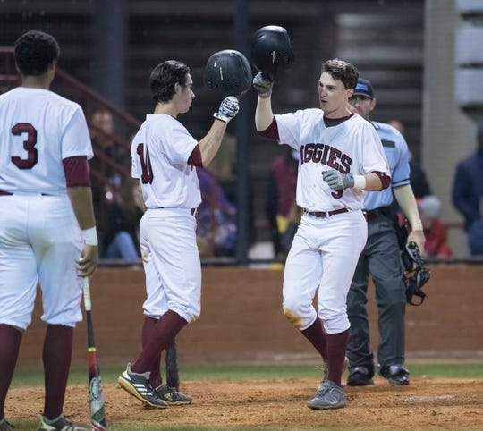 Mason Land (9) is congratulated by teams after hitting a home run as the Aggies take a 2-0 lead during the Pine Forest vs Tate baseball game at Tate High School on Thursday, March 7, 2019.  The Aggies won 4-3.