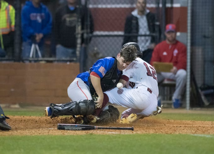 Aaron Noack (12) safely slides into home as catcher Hunter Smith (14) can't find the handle on the ball and the Aggies take a 4-0 lead during the Pine Forest vs Tate baseball game at Tate High School on Thursday, March 7, 2019.  The Aggies won 4-3.