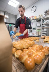 Head bread baker Richard Chapman bags freshly made rolls at Craft Gourmet Bakery in Pensacola on Friday, March 8, 2019.