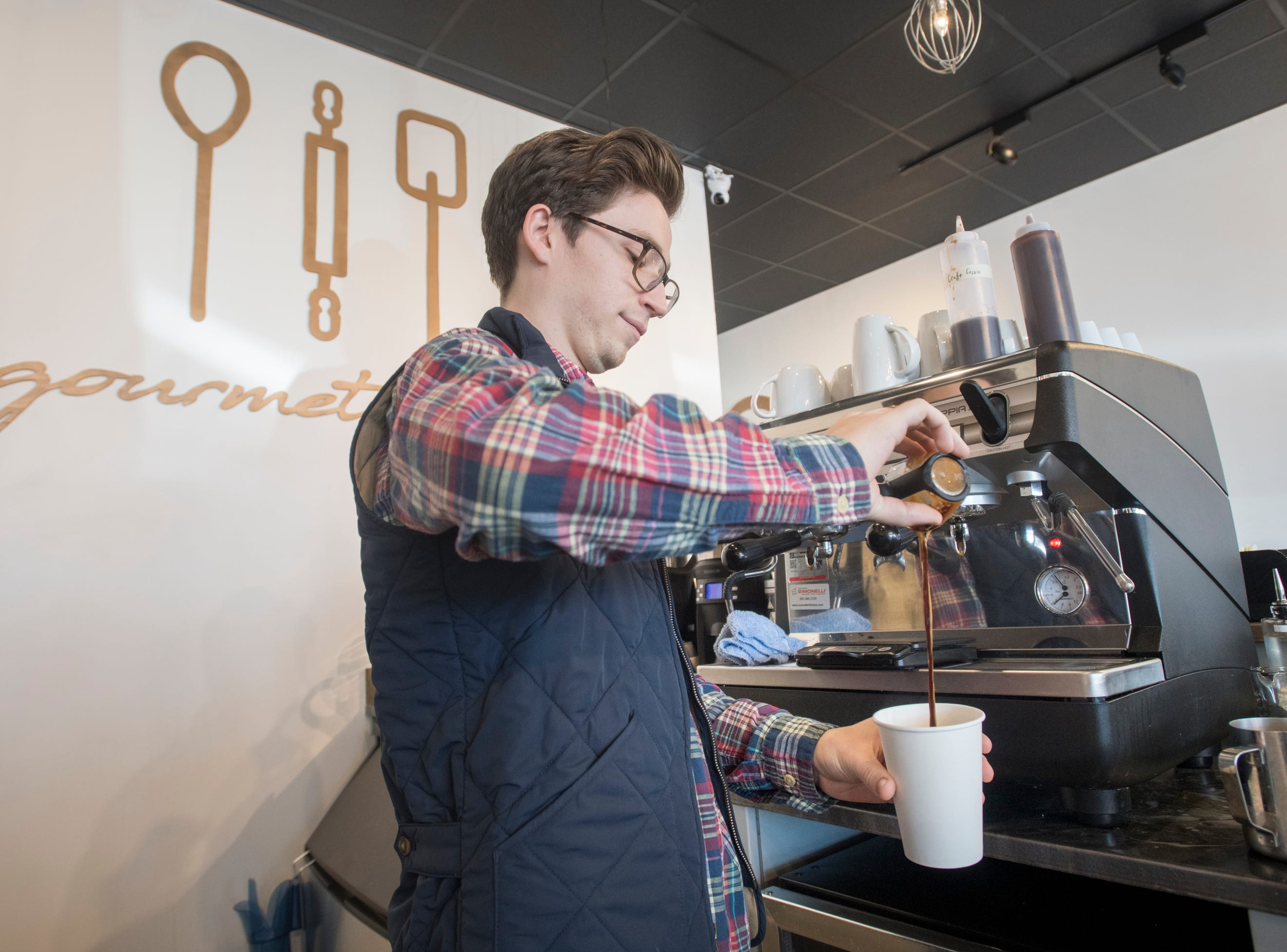 Christian Catalanotto, prepares a latte at Craft Gourmet Bakery in Pensacola on Friday, March 8, 2019.