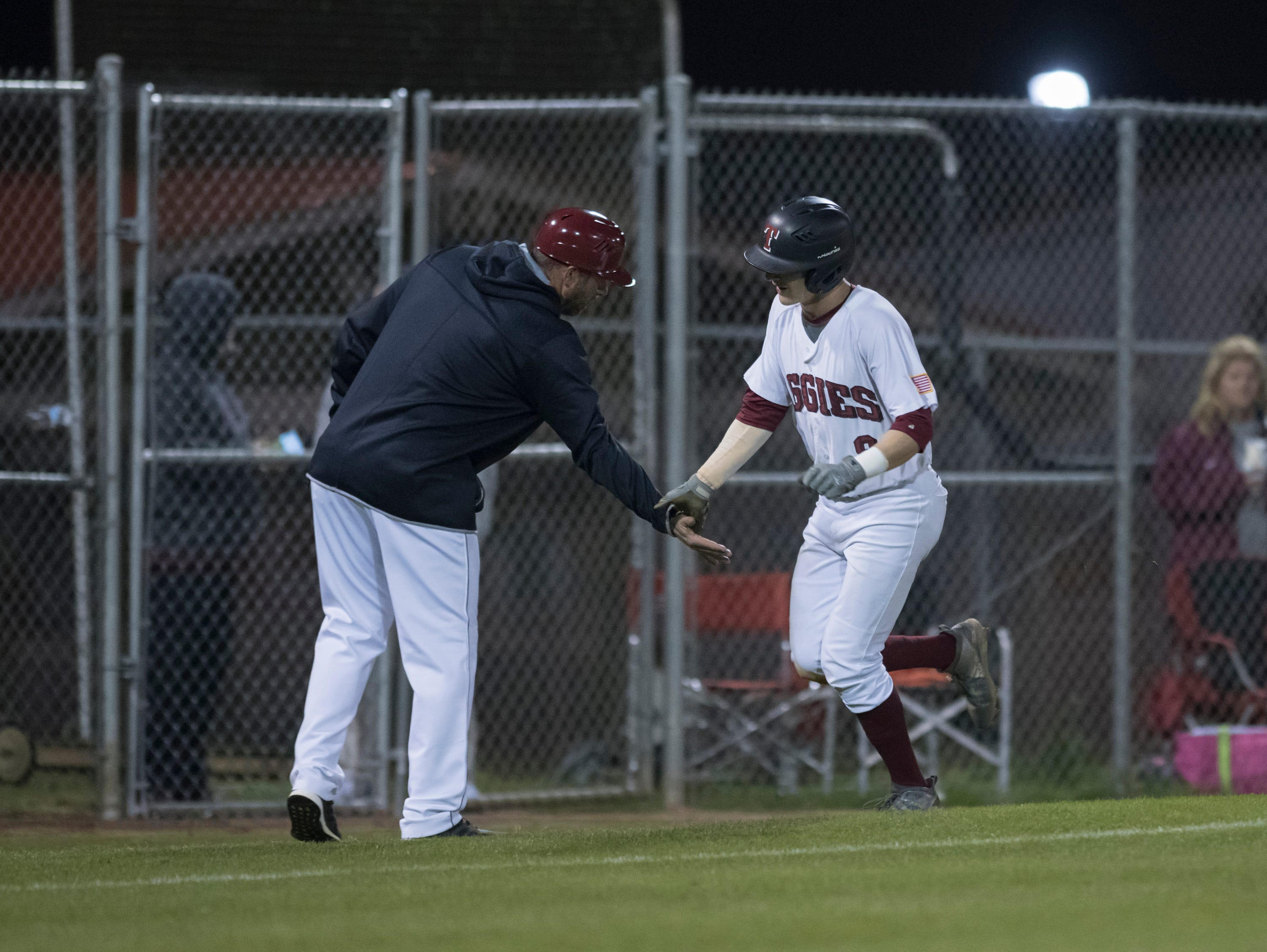 Mason Land (9) is congratulated while he rounds third base on a home run as the Aggies take a 2-0 lead during the Pine Forest vs Tate baseball game at Tate High School on Thursday, March 7, 2019.  The Aggies won 4-3.