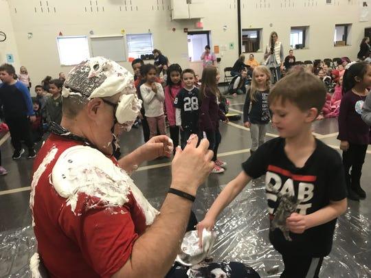 Clearview Elementary School principal Jay Czap is pied in the face by a student of the class who raised the most money for the school's annual fundraiser on March 8, 2019.