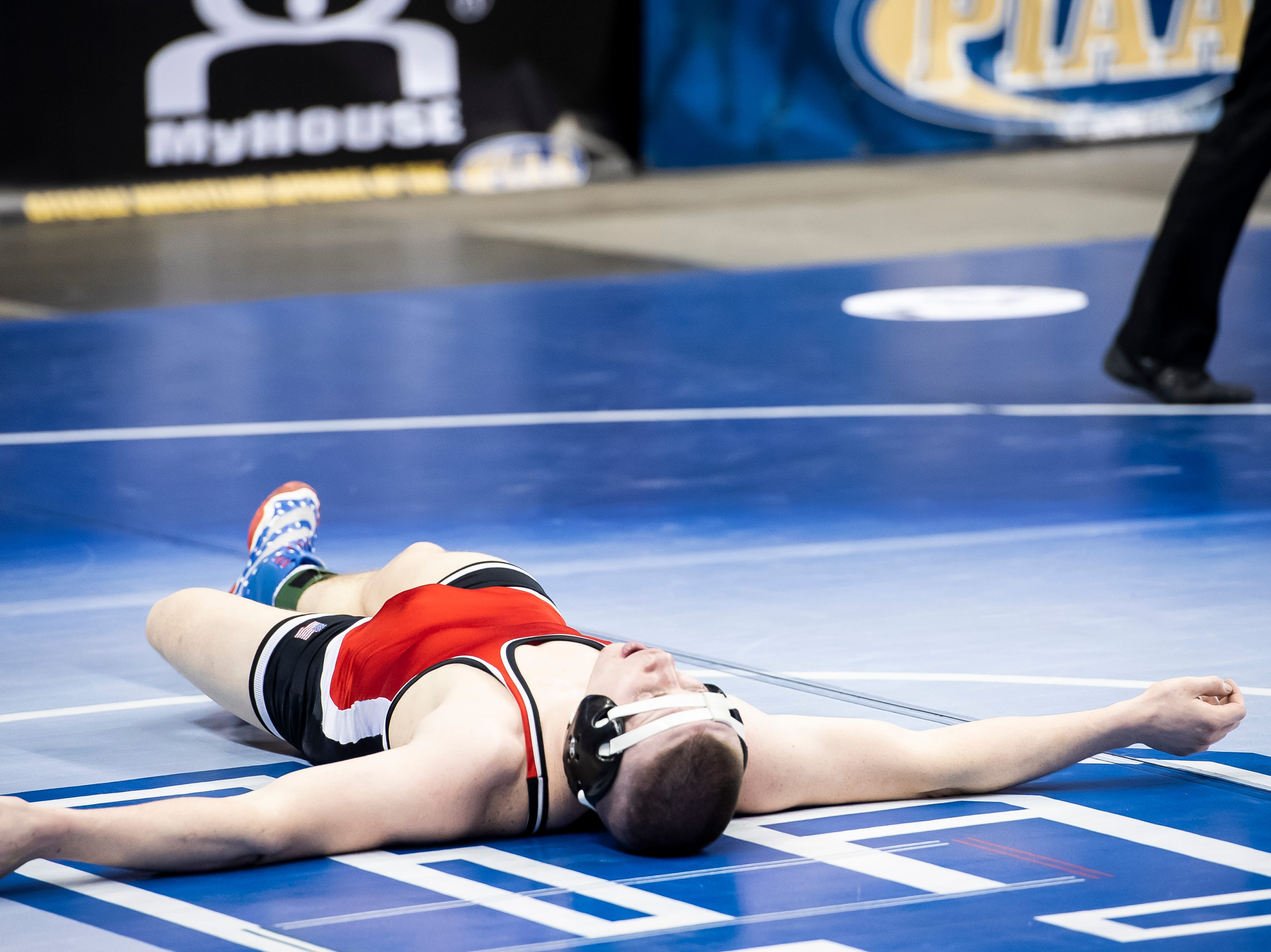 Susquehannock's Colby Romjue lies on the mat after falling to Bellefonte's Ethan Richner during the 3A 152-pound quarterfinal bout at the Giant Center in Hershey Friday, March 8, 2019. Richner won 9-5 TB2.