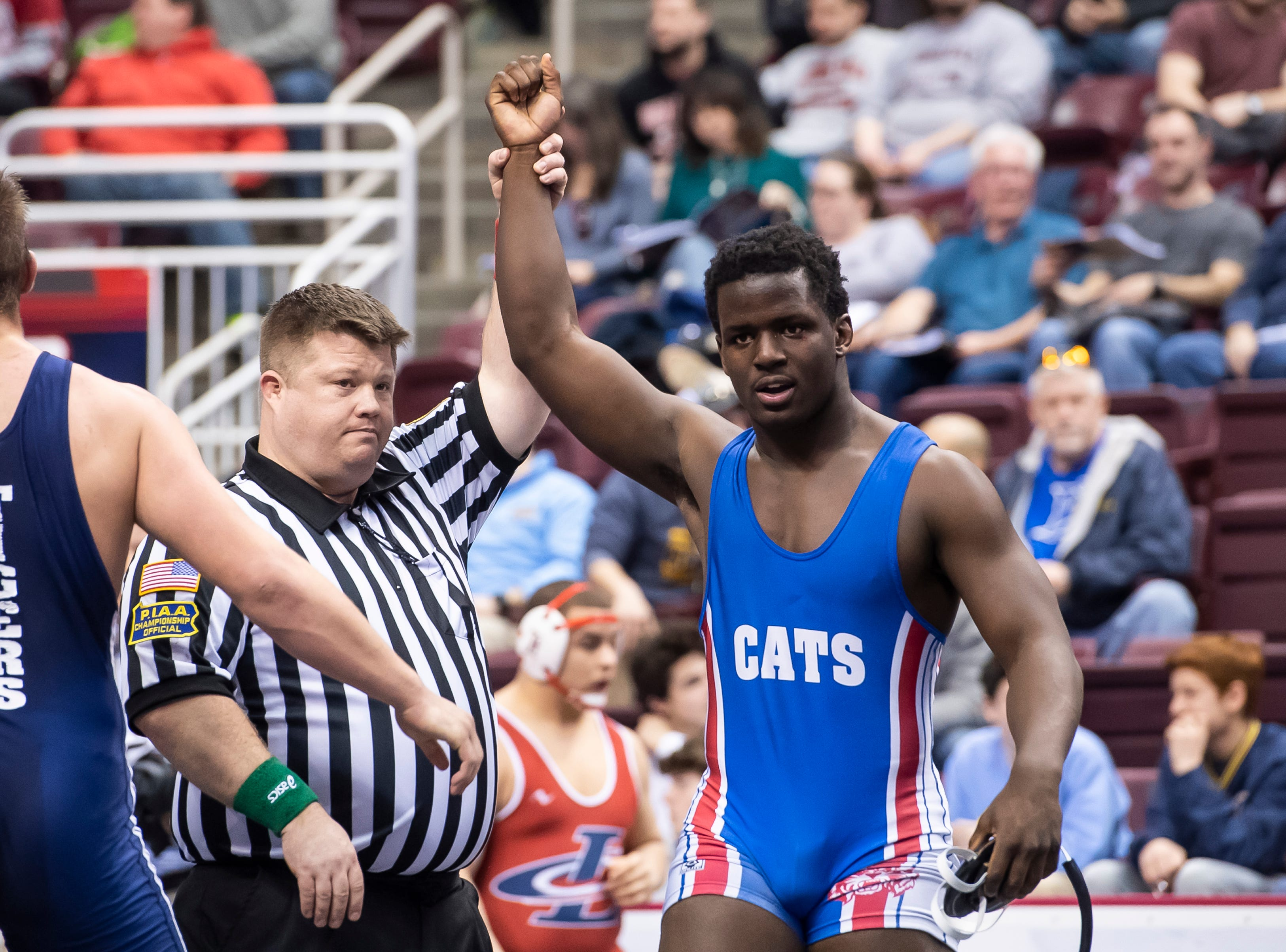 Dallastown's Jamal Brandon has his arm raised after defeating Hollidaysburg's Gus Dellinger during a 3A 220-pound second round consolation bout at the Giant Center in Hershey Friday, March 8, 2019. Brandon won in sudden victory 5-3.