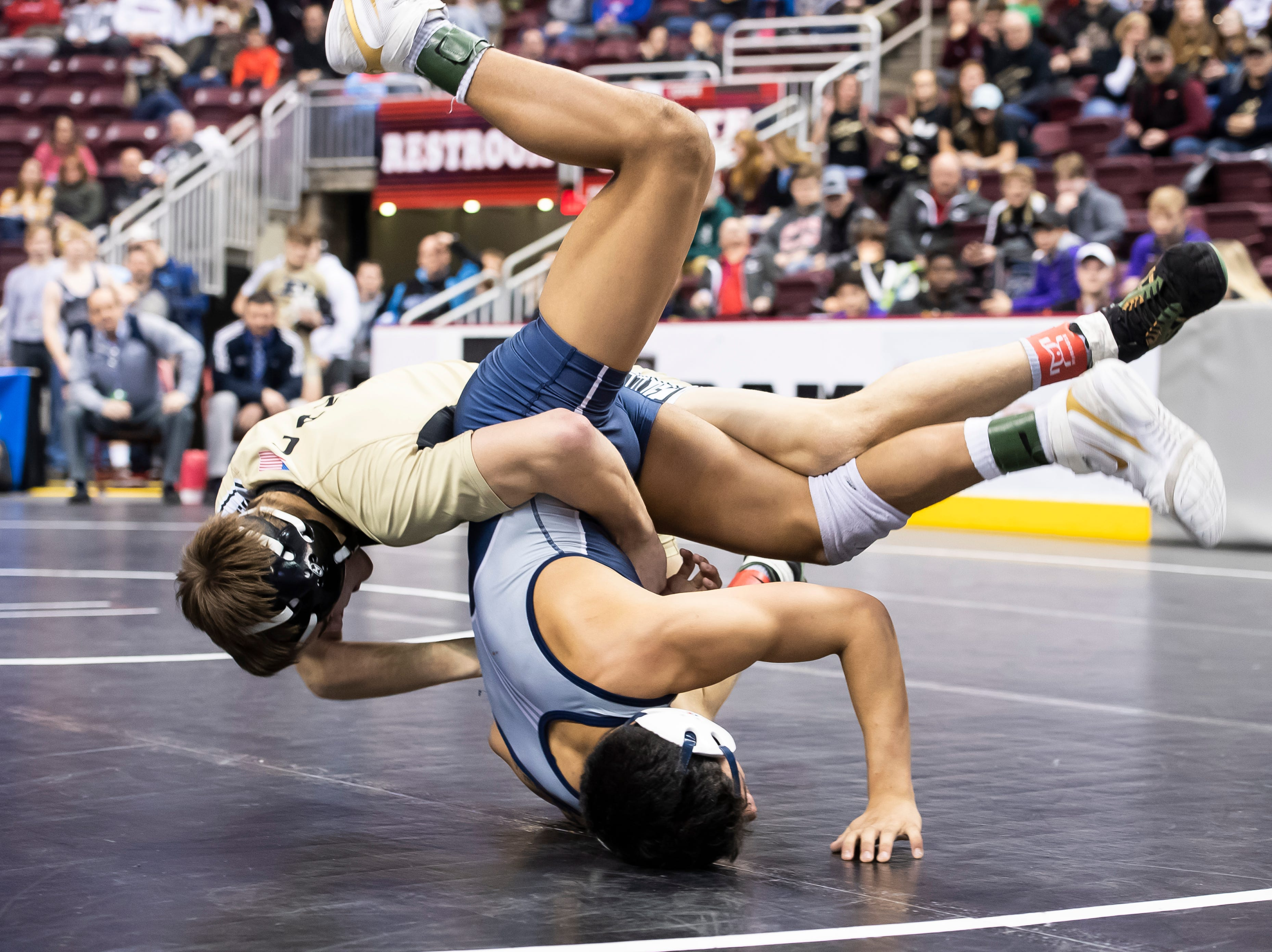 Biglerville's Eli Tuckey, top, wrestles Newport's Dorian Gonzalez during a 132-pound second round consolation bout at the Giant Center in Hershey Friday, March 8, 2019. Tuckey won in sudden victory 9-7.