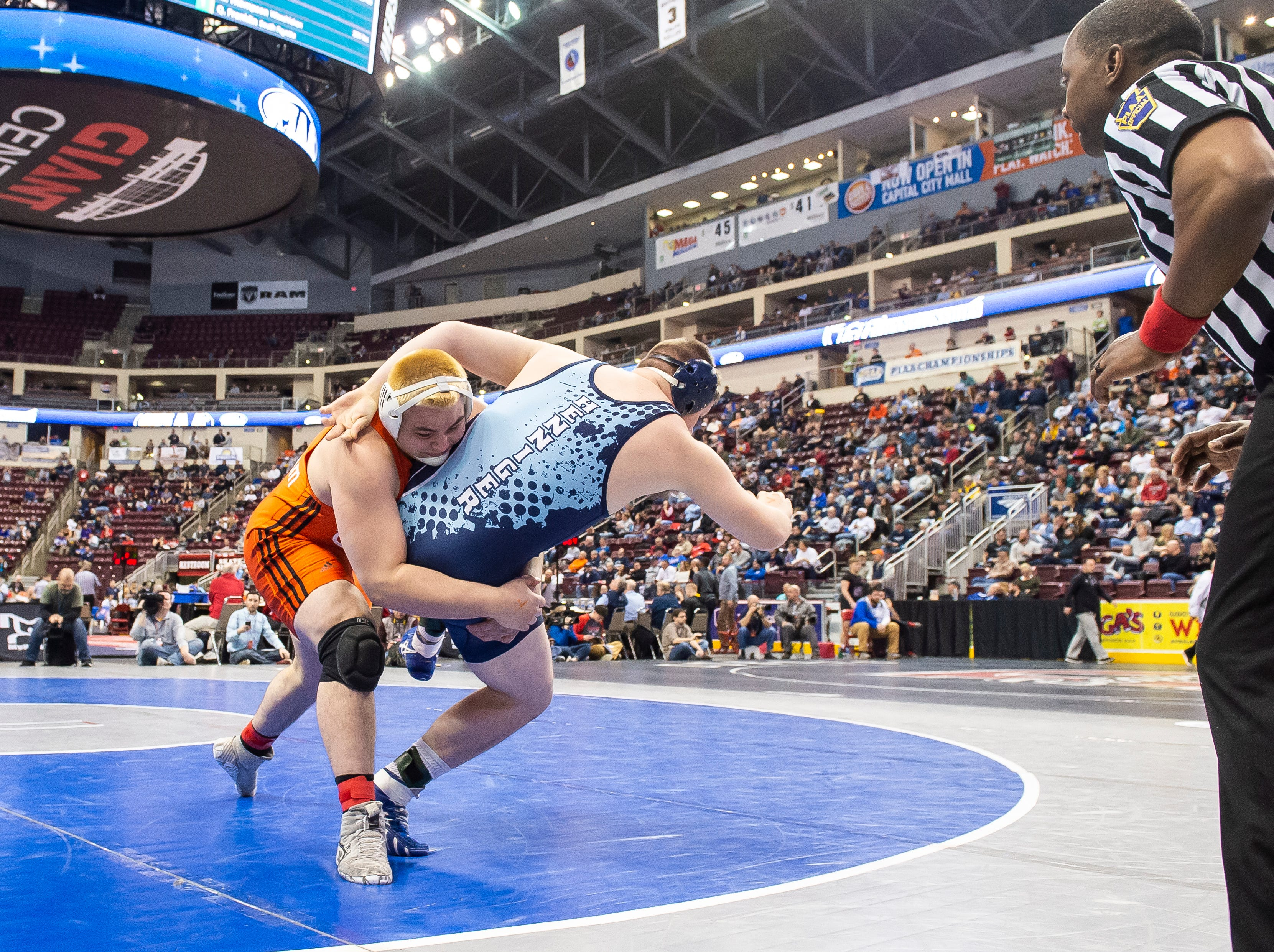 Central York's Michael Wolfgram wrestles Dallas' Shawn Henninger onto his back during the 3A 285-pound quarterfinal bout at the Giant Center in Hershey Friday, March 8, 2019. Wolfgram won by fall at 1:32.