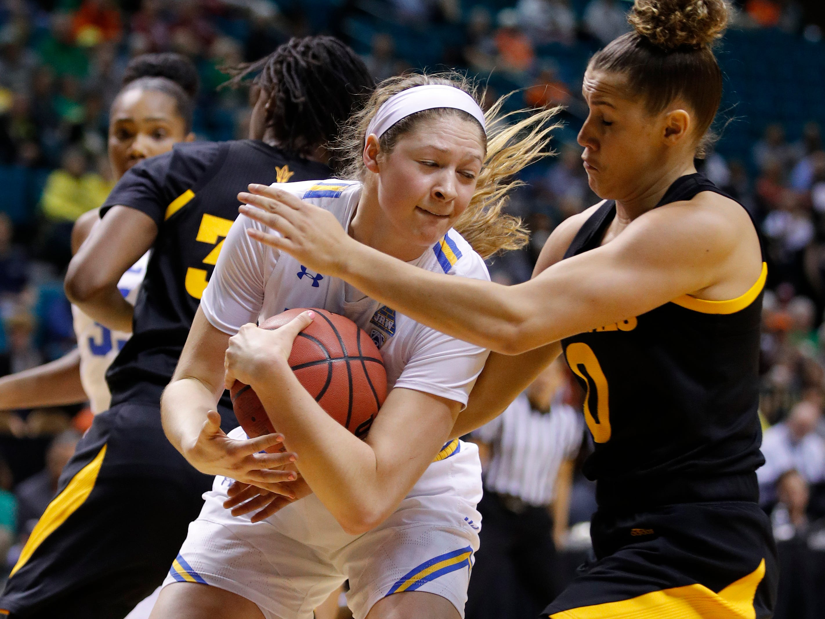 Arizona State's Taya Hanson, right, and UCLA's Lindsey Corsaro battle for a rebound during the first half of an NCAA college basketball game at the Pac-12 women's tournament Friday, March 8, 2019, in Las Vegas.