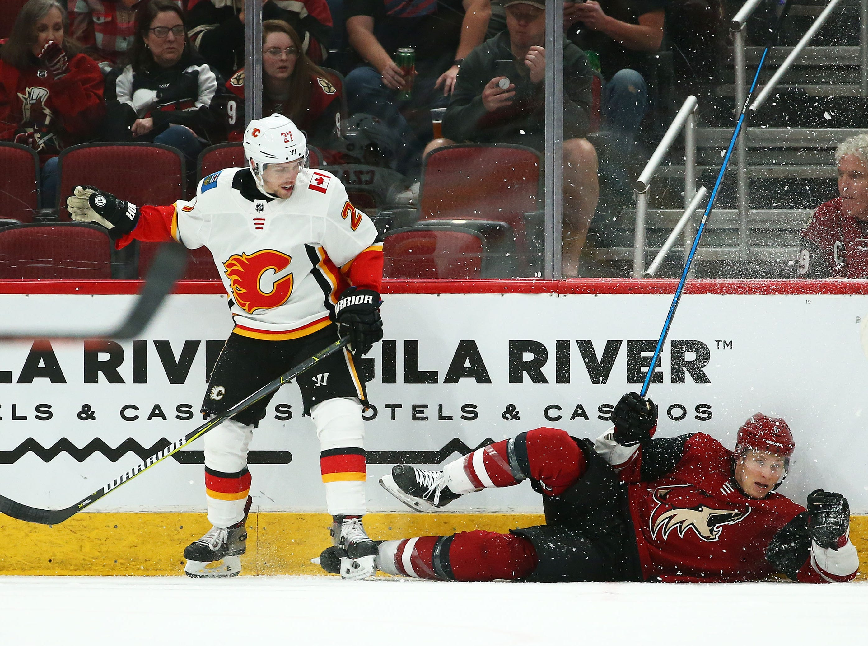 Calgary Flames center Austin Czarnik (27) checks Arizona Coyotes defenseman Jakob Chychrun (6) in the second period on Mar. 7, 2019, at Gila River Arena in Glendale, Ariz.