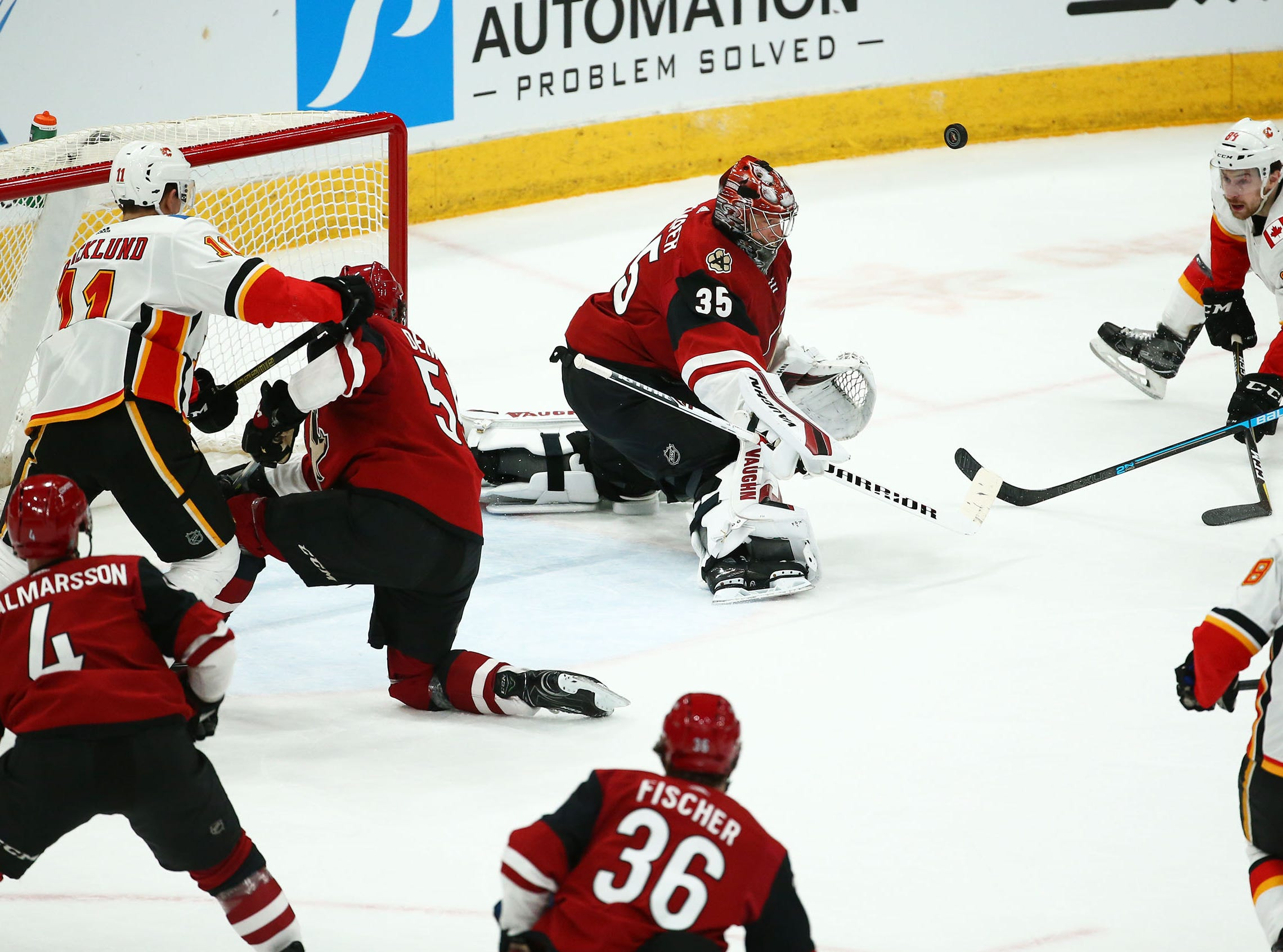 Arizona Coyotes goaltender Darcy Kuemper (35) blocks a shot by the Calgary Flames in the first period on Mar. 7, 2019, at Gila River Arena in Glendale, Ariz.