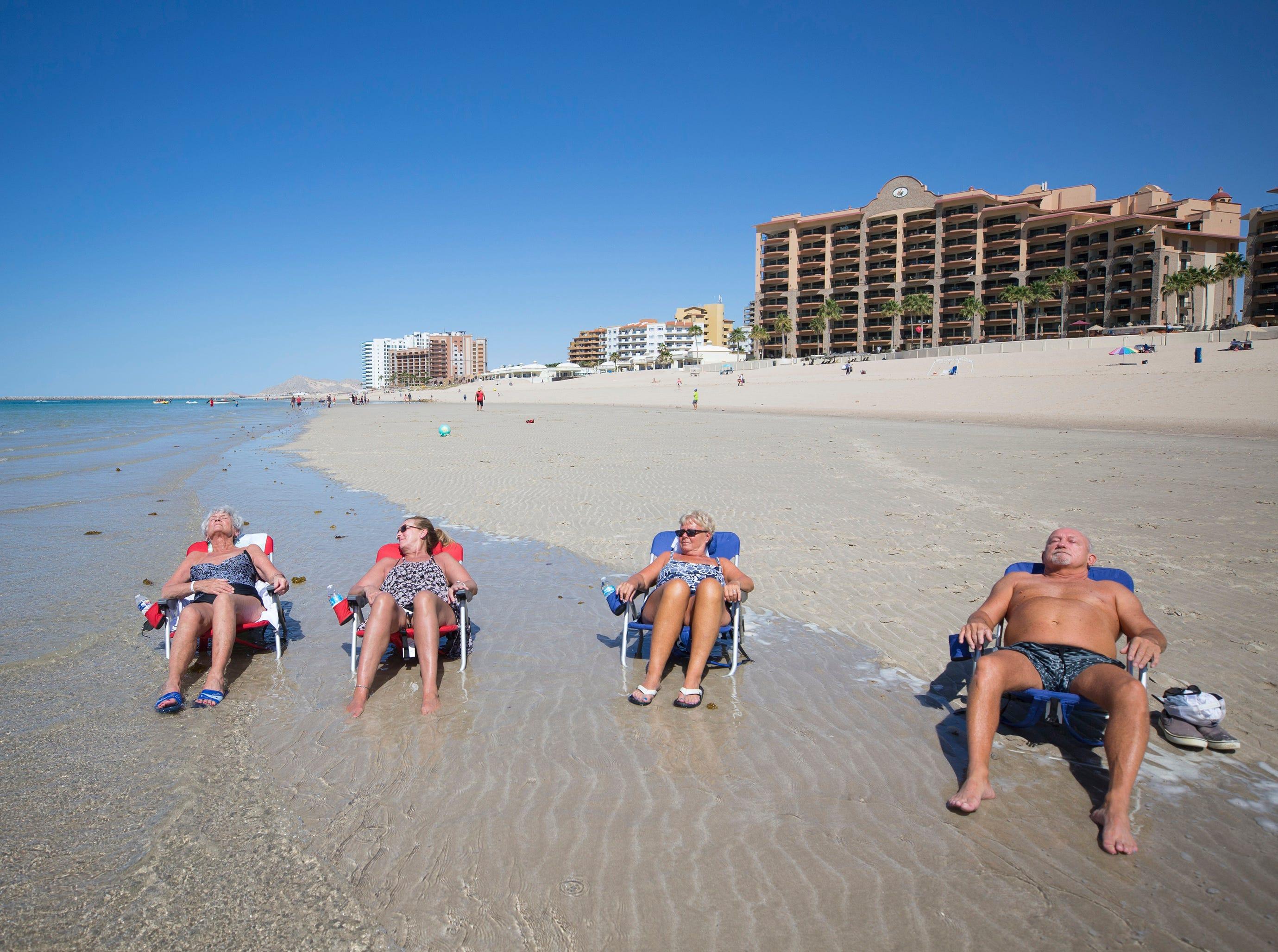 Maureen Clarke, left, Cathy Hein, Ann Shrug and her husband, David, from Canada, soak in the sun on Sandy Beach in Puerto Penasco, Mexico.