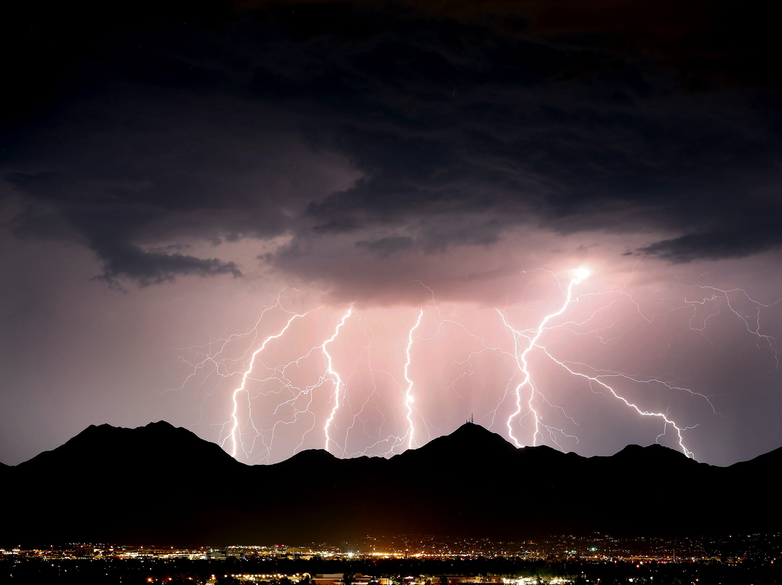 Lightning fires across the desert sky over the McDowell Mountains during a monsoon storm in Scottsdale, AZ.