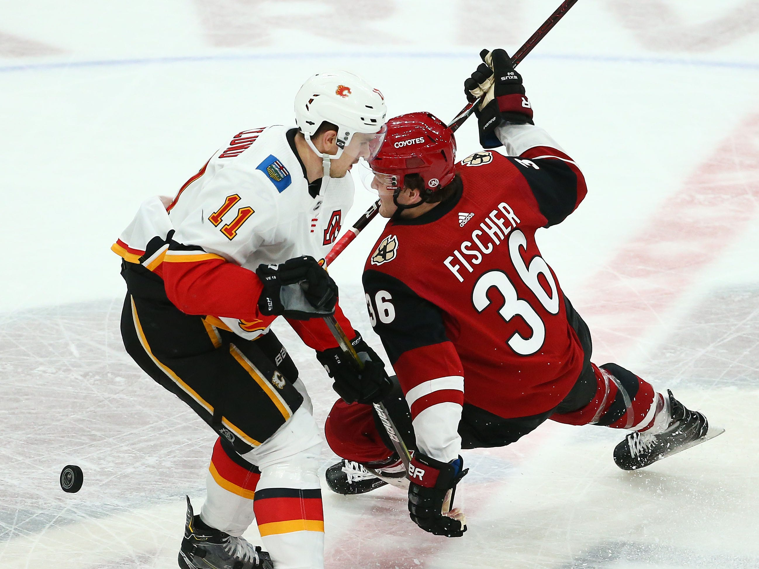 Calgary Flames center Mikael Backlund (11) cross-checks Arizona Coyotes right wing Christian Fischer (36) in the first period on Mar. 7, 2019, at Gila River Arena in Glendale, Ariz.