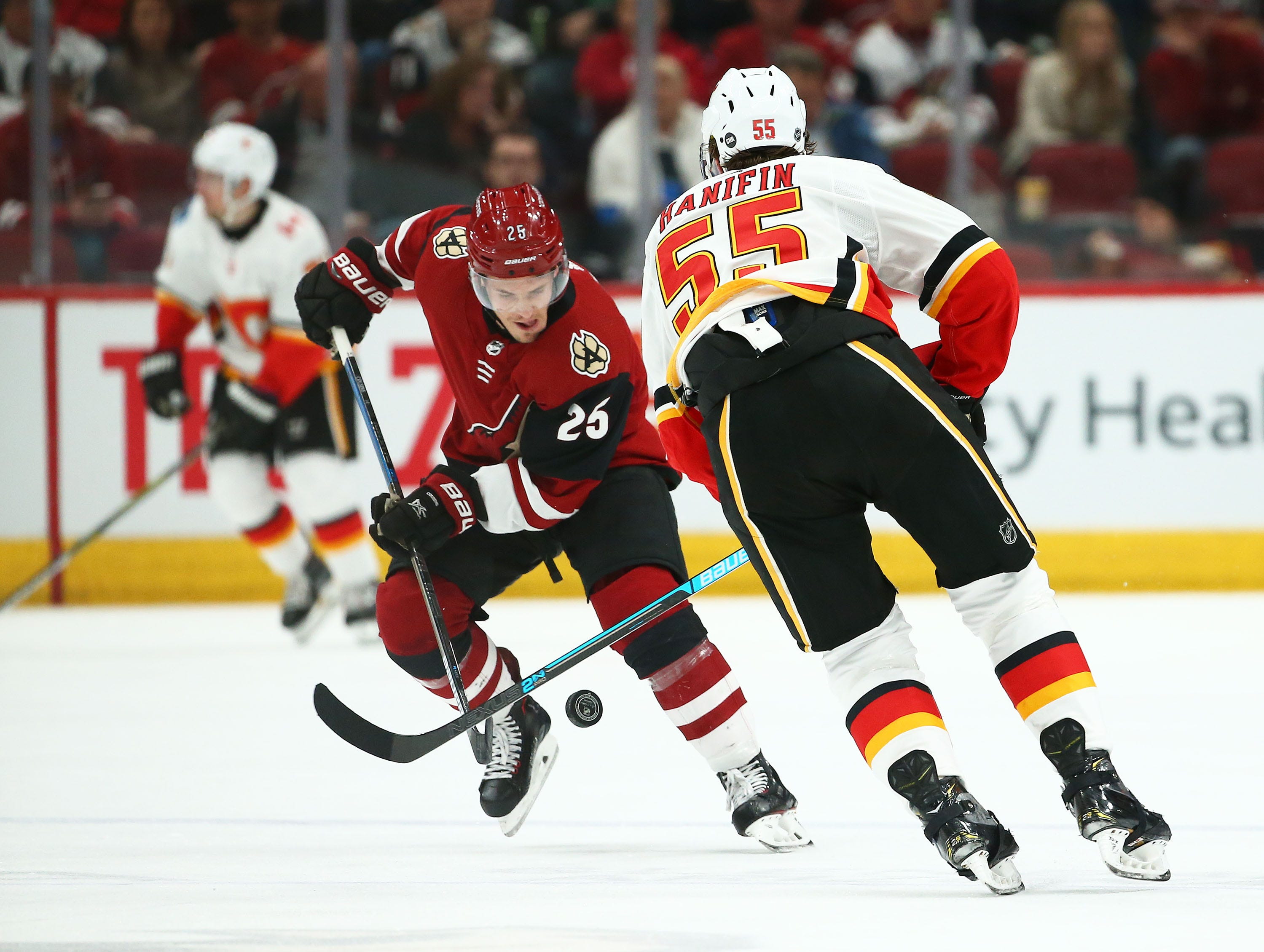 Arizona Coyotes center Nick Cousins (25) and Calgary Flames defenseman Noah Hanifin (55) battle for the puck in the second period on Mar. 7, 2019, at Gila River Arena in Glendale, Ariz.