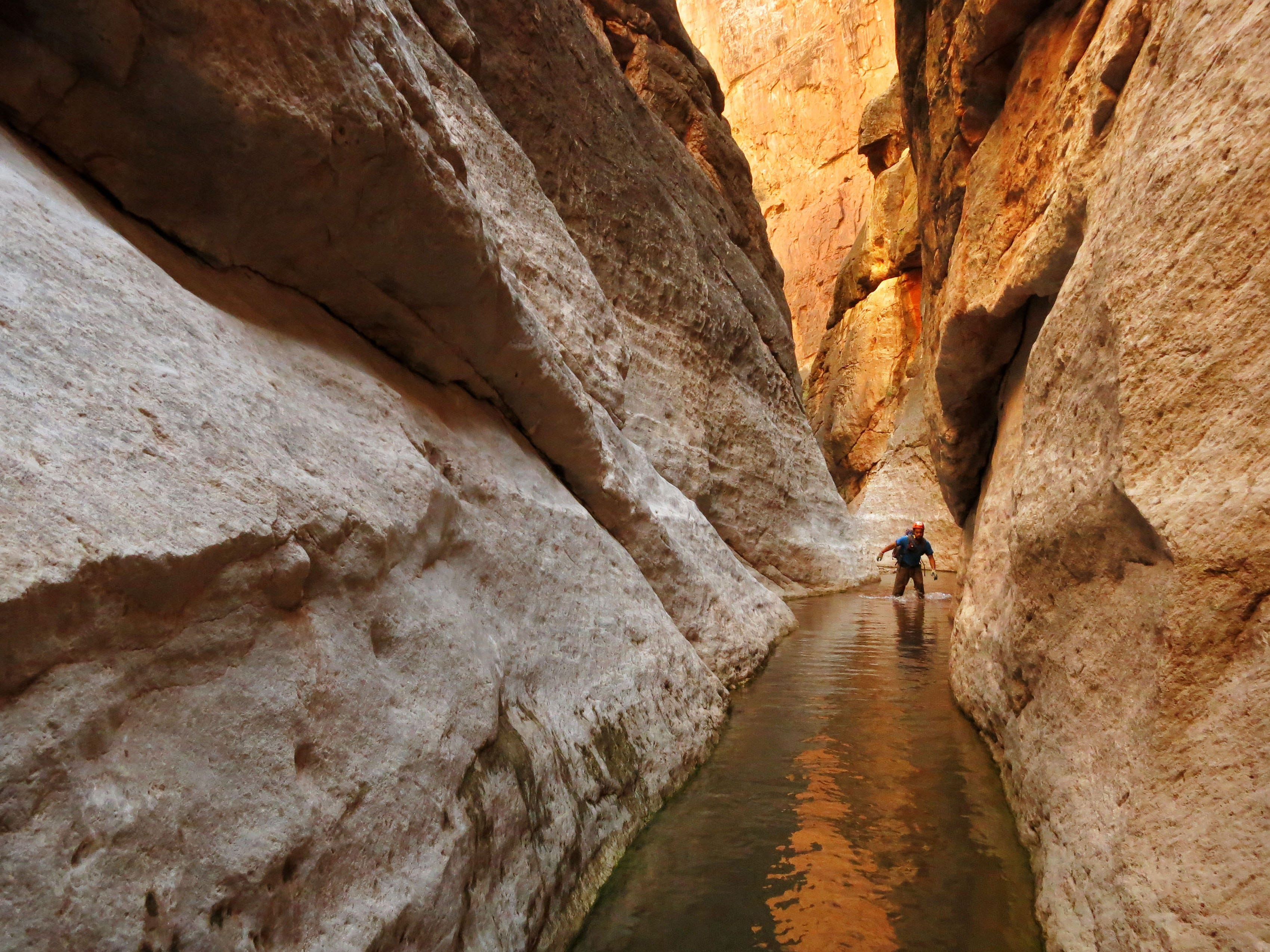 Eric Luth wades through water in the redwall narrows of a side canyon of the Colorado River in Grand Canyon National Park. Hundreds of side canyon drainages meet the Colorado River in Grand Canyon and offer a glimpse into something not impacted by Glen Canyon Dam.
